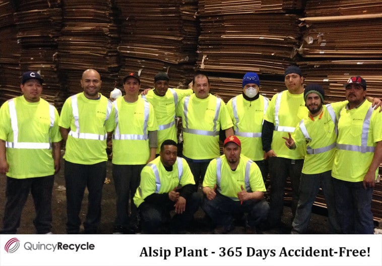 Several Quincy recycle workers celebrate safety wearing yellow safety clothing in Alsip, IL.