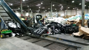 Several people work on a multi-commodity recycling sorting line at a Quincy Recycling facility.