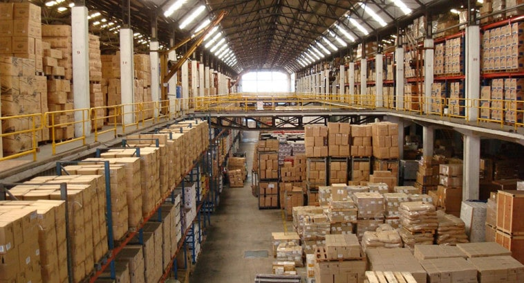 Interior of a recycling warehouse with two stories of packaged and stacked material.