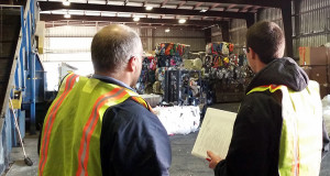 Two men in safety vests look on towards stacks of recycled material inside a recycling facility.