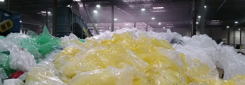 Large piles of green, yellow, and white plastic materials.