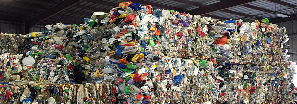 Large bales of multi-color commingled plastic material.