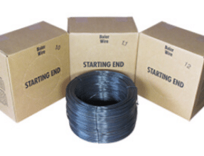 Large spool of dark box wire in front of three cardboard boxes.