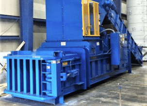Large blue horizontal baler used for processing recycled materials.