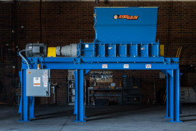 Large blue shredder used for processing recycled materials.