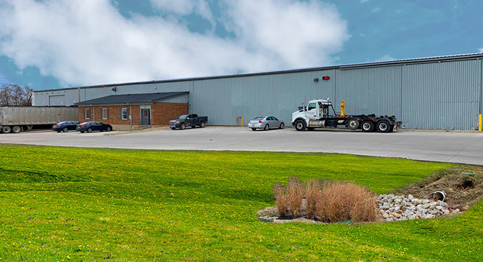 Large grey industrial building with multiple cars and tractor trailers parked outside.
