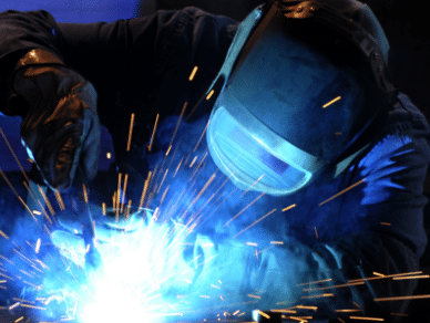 Factory working wearing a welding mask is welding material.