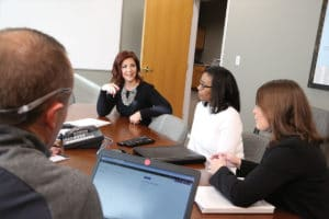 Three professional business women having a discussion around a conference room table.