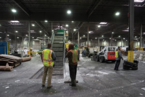 Three workers in safety vests supervise machine operation in a recycling facility.