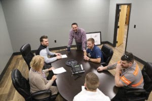 Several Quincy Recycle employees having a discussion around a brown conference room table.
