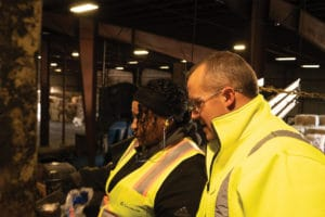 Two workers in yellow safety vests looking at recycled material.
