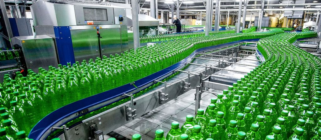 Hundreds of green plastic bottles in an assembly line.
