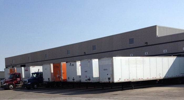 Large grey building with multiple trailers parked at loading docks.
