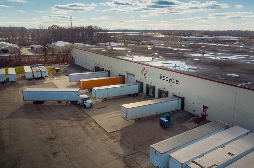 Overhead view of a Quincy Recycle location with several cargo trailers parked at loading docks.