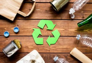 Green recycled symbol on a wood table surrounded by recyclable materials.