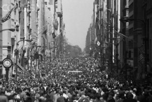 Black and white photo of long crowded street with large buildings on the left and right sides